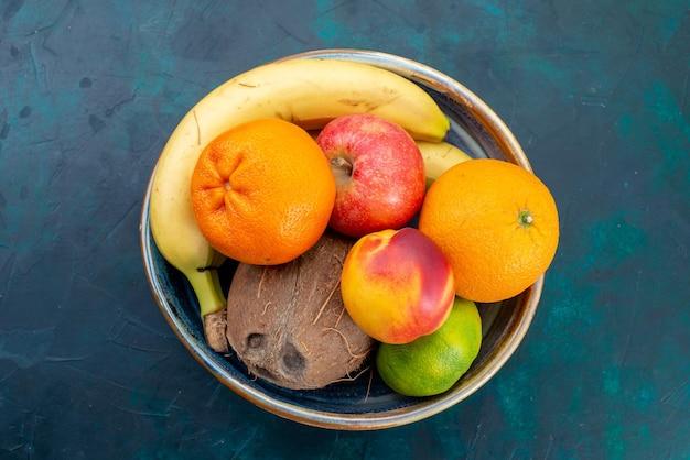 Vista dall'alto composizione di frutta mandarini banane mele e cocco sulla scrivania blu scuro