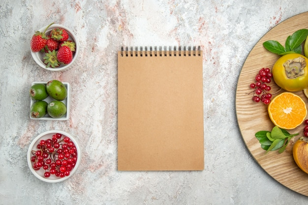 白いテーブルの上のメモ帳でトップビューの果物の構成果物熟した木の色新鮮