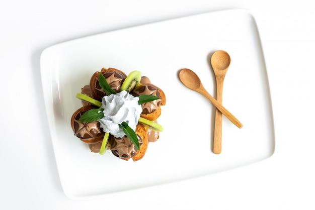 Un dessert alla frutta con vista dall'alto ha progettato torte con kiwi a fette e crema pasticcera all'interno della scrivania bianca insieme a cucchiai di legno gelato dolce frutta