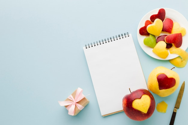 Top view of fruit heart shapes with notebook and present