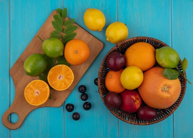 Top view fruit mix in a basket of grapefruit  oranges  lemons  lime and cherry plum with a cutting board on a turquoise background
