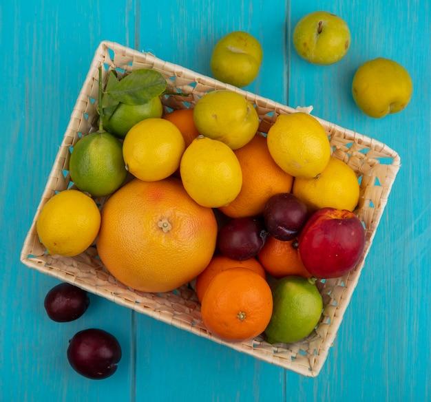 Vista dall'alto mix di frutta pompelmo limoni limette arance pesche e prugne in un cesto su uno sfondo turchese