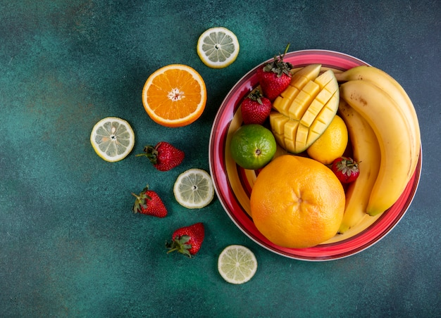 Вид сверху фруктовый микс в тарелке из манго, клубники, лайма и апельсина на зеленом фоне