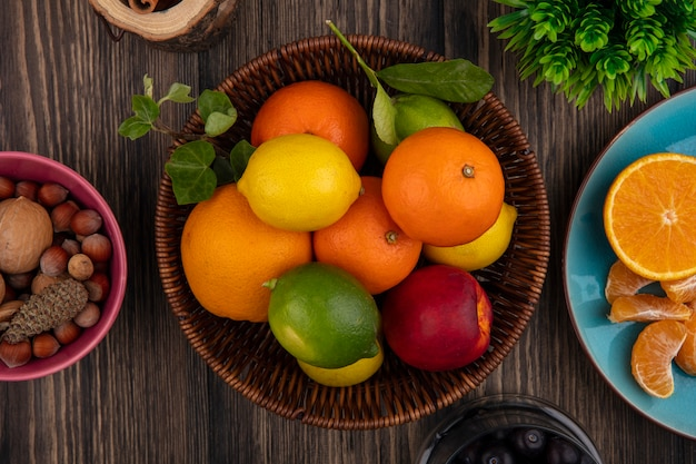 木製の背景にバスケットオレンジレモンライムと桃のトップビューフルーツミックス