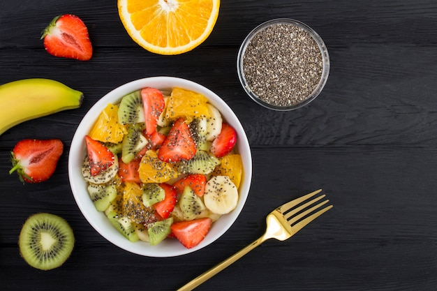 Top view of fruit salad with chia seeds and ingredients