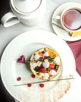 Vista dall'alto di macedonia di frutta con banane di ananas e bacche su un piatto bianco
