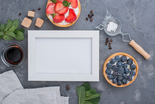 Top view of fruit tarts with frame and honey