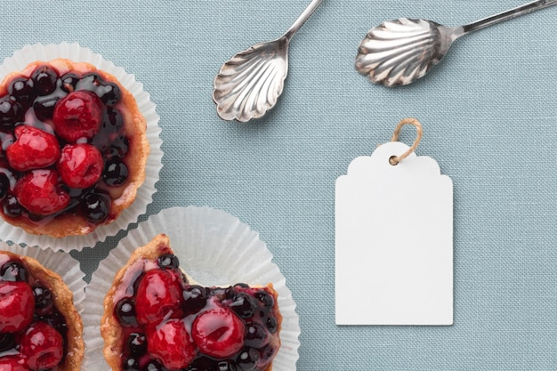 Top view of fruit tarts with spoons and tag