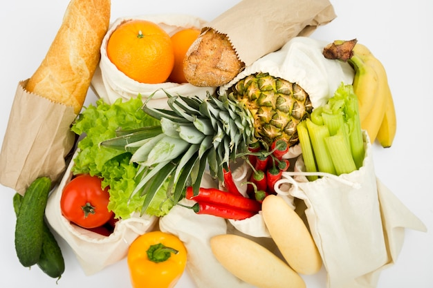Top view of fruit and vegetables in reusable bags with bread