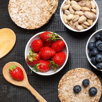 Вид сверху фрукты и фисташки в мисках