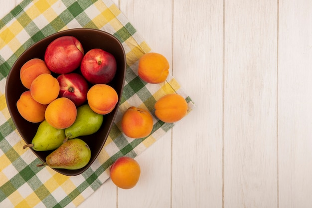 Top view of fruits as apricot peach pear in bowl on plaid cloth and on wooden background with copy space