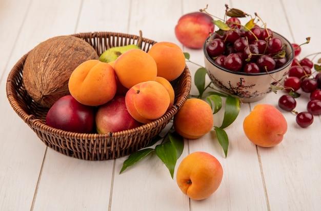 Vista dall'alto di frutta come noce di cocco albicocca pesca pera nel cestino e ciotola di ciliegie con foglie su sfondo di legno