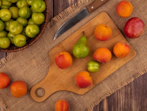 Vista dall'alto di frutta come albicocca pera prugna sul tagliere con pesca e coltello su tela di sacco e cesto di prugne su sfondo di legno