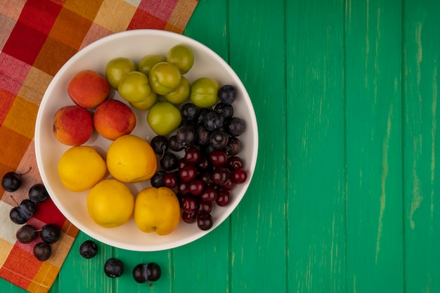 Top view of fruits as apricots plums and cherries in bowl with sloe berries on plaid cloth and on green background with copy space