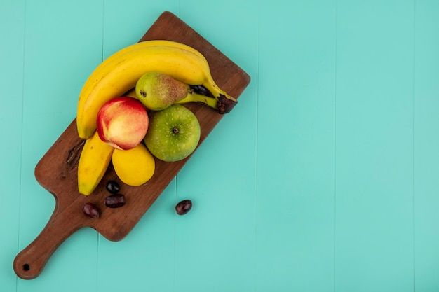 Top view of fruits as banana apple lemon peach grape berries on cutting board on blue background with copy space