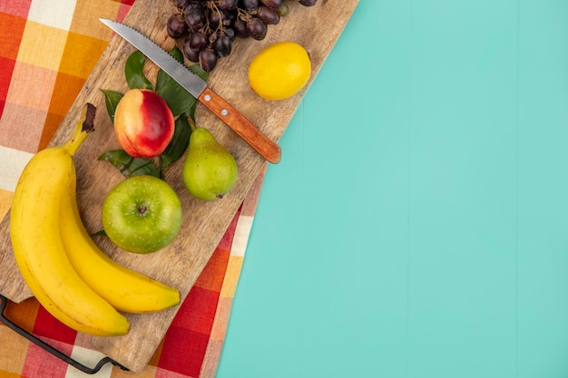 Top view of fruits as banana apple peach pear lemon grape with knife and leaves on cutting board on plaid cloth and blue background with copy space