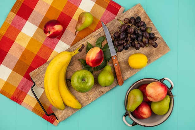 Top view of fruits as banana apple peach pear lemon grape with knife and leaves on cutting board on plaid cloth with pot of pear peach on blue background