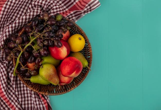 Vista dall'alto di frutta come cesto di pera pesca limone uva su sfondo blu con copia spazio