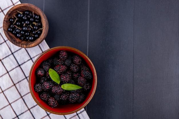 Vista dall'alto di frutti come ciotole di prugnola e mora sul panno plaid sulla superficie nera
