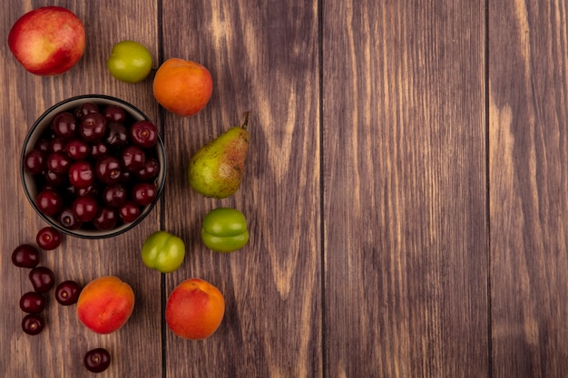 Top view of fruits as cherries in bowl and pattern of peach plums apricots pear cherries on wooden background with copy space