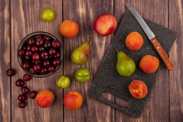 Vista dall'alto di frutti come ciliegie nella ciotola e il modello di pesche prugne albicocche pere ciliegie con coltello sul tagliere e su sfondo di legno
