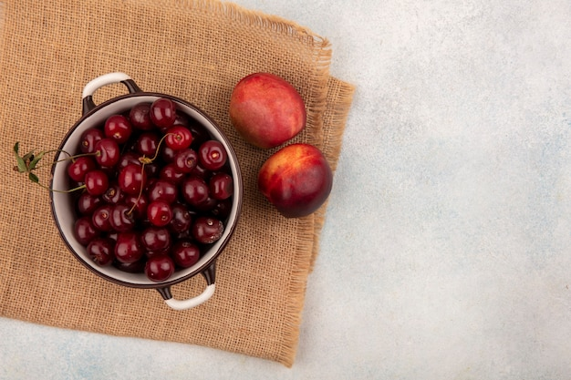 Top view of fruits as cherries in bowl and peaches on sackcloth and white background with copy space