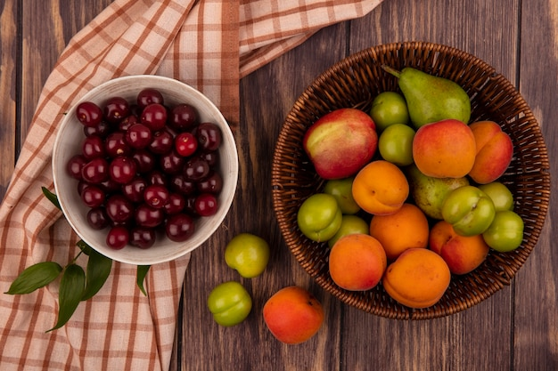 Top view of fruits as cherries in bowl on plaid cloth and basket of peach apricot pear plum on wooden background