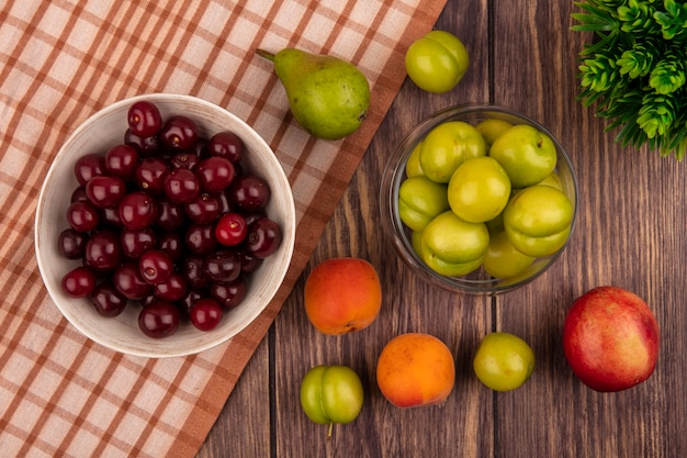 Top view of fruits as cherries in bowl on plaid cloth and plums in jar with apricots plums peach pear on wooden background