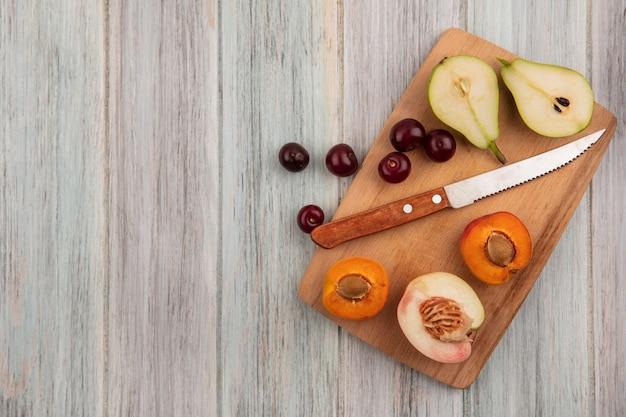 Vista dall'alto di frutti come ciliegie e pera albicocca tagliata a metà e pesche con coltello sul tagliere su sfondo di legno con spazio di copia
