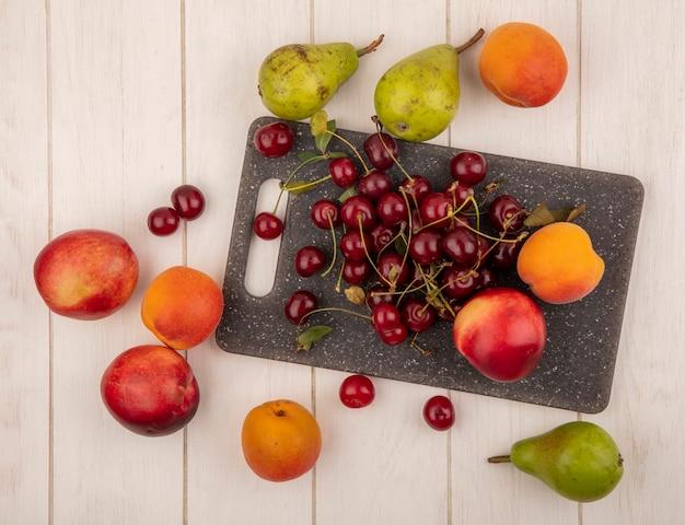 Vista dall'alto di frutti come ciliegie e pesche sul tagliere e modello di pere, ciliegie e pesche su sfondo di legno