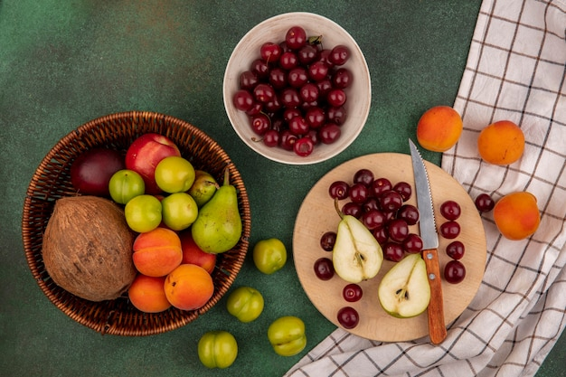 Vista dall'alto di frutti come ciliegie pera cocco prugna albicocca pesca con coltello nel cestello e sul tagliere su plaid panno su sfondo verde