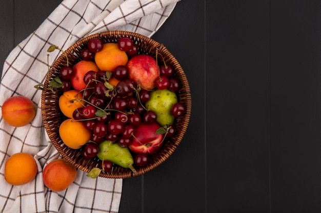 Top view of fruits as cherry peach apricot pear in basket and on plaid cloth on black background with copy space