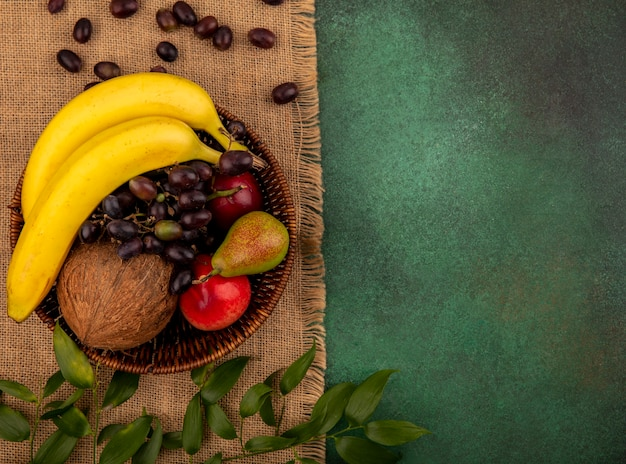 Top view of fruits as coconut banana grape pear peach in basket with leaves on sackcloth on green background with copy space