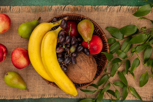 Top view of fruits as coconut banana grape pear peach in basket with leaves on sackcloth on green background