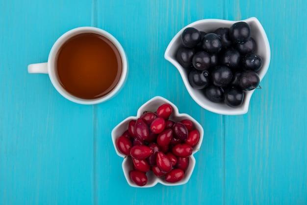 Vista dall'alto di frutti come bacche di corniolo e prugnole in ciotole con tazza di tè su sfondo blu