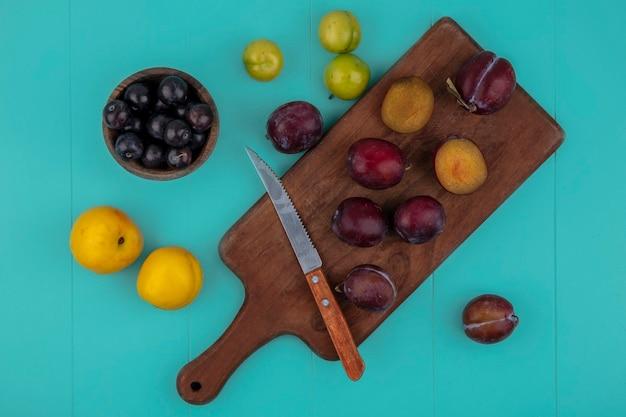 Vista dall'alto di frutti tagliati e interi pluots e coltello sul tagliere con prugne nectacots e ciotola di acini d'uva su sfondo blu