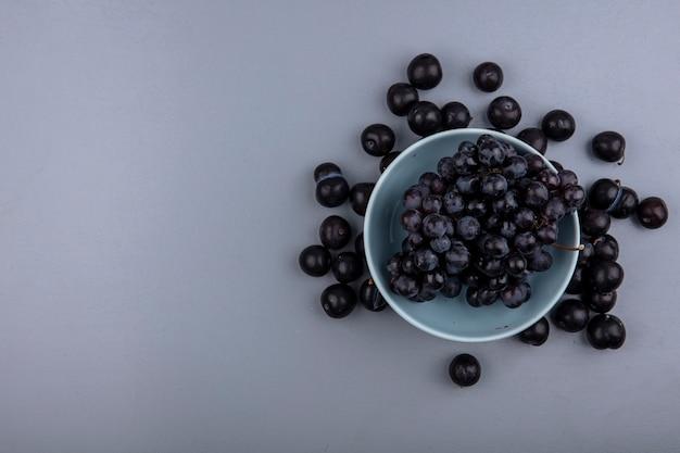 Vista dall'alto di frutti come uva nella ciotola e bacche di prugnole su sfondo grigio con spazio di copia