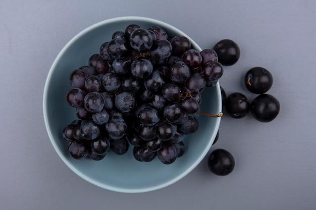 Vista dall'alto di frutti come uva nella ciotola e bacche di prugnole su sfondo grigio