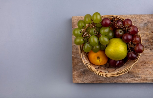 Top view of fruits as grape nectacot pluot in basket on cutting board on gray background with copy space