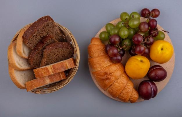 Vista dall'alto di frutta come uva nectacot e pluot con croissant sul tagliere e cesto di pane su sfondo grigio