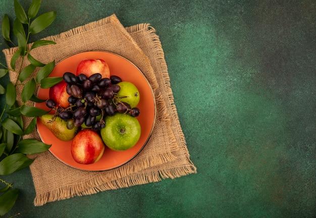 Vista dall'alto di frutti come uva pesca mela pera nel piatto con foglie su tela di sacco su sfondo verde con copia spazio