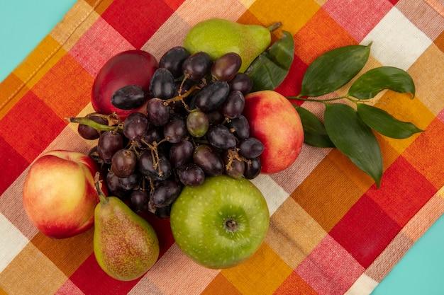 Vista dall'alto di frutti come uva pesca mela pera con foglie su sfondo di panno plaid