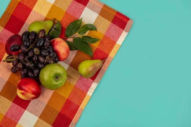 Vista dall'alto di frutta come uva pesca mela pera con foglie su un panno plaid e sfondo blu con spazio di copia