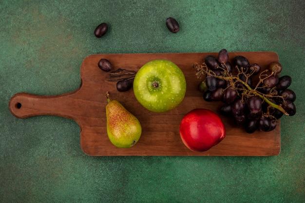 Vista dall'alto di frutti come uva pesca pera mela sul tagliere su sfondo verde