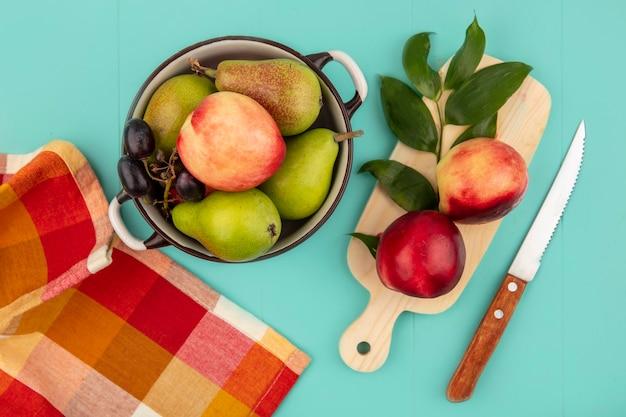 Vista dall'alto di frutti come uva pesca pera in pentola e pesche con foglie sul tagliere con panno plaid e coltello su sfondo blu