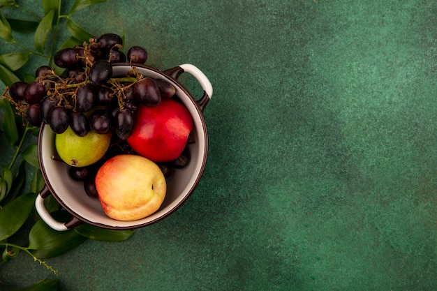 Top view of fruits as grape peach pear in pot with leaves on green background with copy space