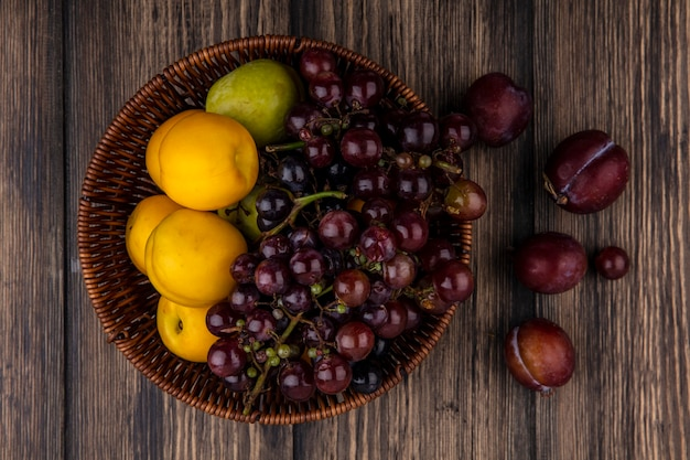 Vista dall'alto di frutti come uva pluot nectacots nel cestello e sapore king pluots su sfondo di legno