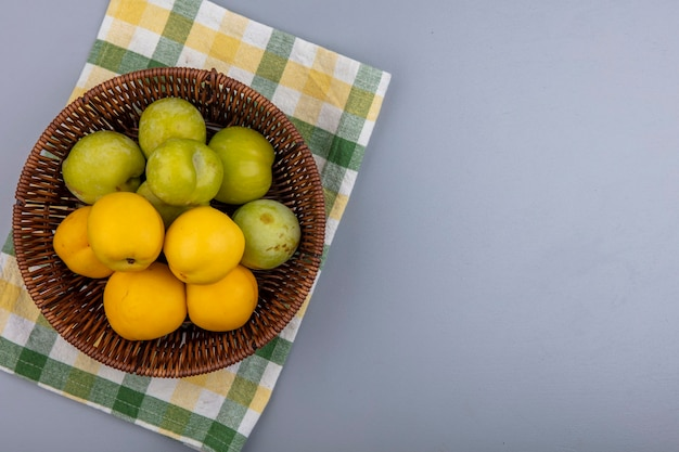 Vista dall'alto di frutti come pluots verdi e nectacots nel cesto su panno plaid su sfondo grigio con spazio di copia