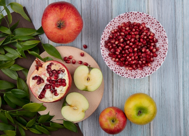 Top view of fruits as half cut apple and pomegranate half on cutting board with leaves on cloth and pomegranate berries in bowl with whole ones on wooden surface