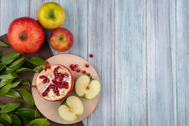 Top view of fruits as half cut apple and pomegranate half on cutting board with whole ones and leaves on cloth on wooden surface